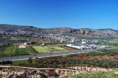 """Khirbet Madrasah, Karmi'el - A view towards the north side is seen below. The mountain ridge in the background is called """"Matlul Zurim"""" (meaning: """"steep cliffs""""), which towers to the height of 570M (350M above the valley). The Arab village of Deir-el-Asad is seen on the left background, and Bi'na (el-Ba'neh) in the center."""