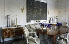 In the dining room, Brice Marden's Glyphs overlooks Louis XVI fauteuils; the antique dining table and the pair of 18th-century French commodes are from Galerie Perrin, and the table lamps are by Christophe Côme from Cristina Grajales Gallery. The exceptional boiserie is by Féau & Cie; Andy Warhol's Knives is propped in a corner.