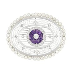 Art Deco Platinum, Amethyst, Enamel, Diamond and Pearl Brooch   The oval mount centering one old European-cut diamond encircled by 6 fancy-shaped amethysts, framed by rose-cut diamonds, within an openwork oval of platinum filigree, surrounded by a stylized key-fret motif applied with white enamel, decorated with 6 small rose-cut diamonds, further framed by seed pearls, circa 1920.