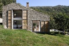 Off Grid Home in Extremadura - Architizer, modern build with old stones, shutters capture passive solar gain.