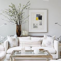 """""""Looking for a creative way to fill the blank wall space behind your sofa? Try adding a narrow console table between the wall and your sofa, then place a tall vase on the table filled with large branches of apple or cherry blossoms and position it adjacent to a generously-sized piece of art or frame."""" —Sarah Richardson 