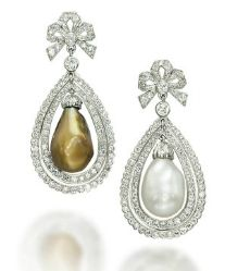 A PAIR OF NATURAL PEARL AND DIAMOND EARRINGS  Set with a drop-shaped natural pearl, measuring approximately 10.3-11.3 x 16.0 mm, and a drop-shaped natural yellowish-brown pearl, measuring approximately 10.3-11.3 x 18.0 mm, each in a pear-shaped flexible diamond-set twin row, to the diamond-set bow top, mounted in platinum.  Christie's.