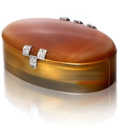 A chalcedony and diamond box, by Boucheron, circa 1920 The oval chalcedony case with rose-cut diamond clasp and hinges, opening to reveal a mirrored lid and concealed polished interior, signed Boucheron Paris, maker's mark, French assay mark, length 6.3cm
