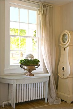 White on White: White walls create a neutral backdrop that lets your furnishings and accents shine. Linen curtains casually drape the front window and drag on the floor. A demilune table with a distressed white finish sits over the radiator. French Decor, French Country Decorating, Swedish Decor, Country French, Swedish Style, French Farmhouse, European Style, Radiator Shelf, Radiator Ideas