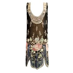 A 1920s beaded flapper dress. Sheer black silk features an elaborately art deco beaded neck and hemline.  Silk, crystal and glass Front 1 Private Collection