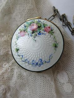 Vintage Deco 20s enameled finger ring compact locket in sterling silver. This pretty 1920s enameled sterling locket compact retains its original finger ring chain. The locket is accented with beautiful enameling with floral embellishments. It measures just over 1 in diameter with nice
