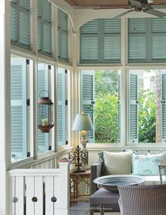 Turquoise shutters enclose a light-filled porch.