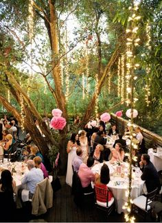Trees decorated with fairy lights and pink tissue pompoms ...beautiful!