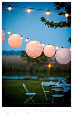 Una boda de postal. Ideas para decorar bodas con luces colgantes de manera sencilla y hermosa para bodas en verano haciendo uso de lamparas de papel y bombillos.