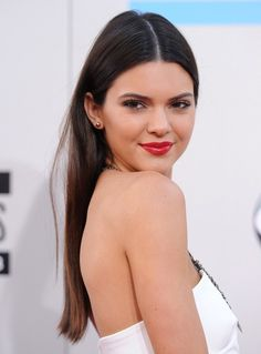 Kendall Jenner works a 70's sleek middle part and red lip