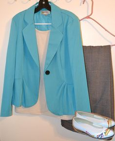 A metallic white top under a teal blazer with grey pants with a hint of teal and multicolored vintage kitten heels.