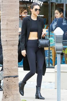Kendall Jenner wears a crop top, long black coat, leggings, Alexander Wang boots, a mini Givenchy duffle, thin choker, and aviator sunglasses