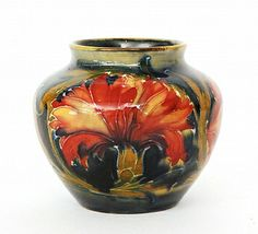 William Moorcroft - Spanish - A vase of shouldered ovoid form with a shallow collar neck decorated with stylised flowers and foliage over an ochre, green and blue washed ground, impressed marks and green full painted signature, height 6.5cm