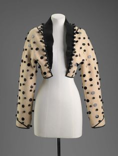 Woman's bolero | United States, circa 2000 | Designed by Geoffrey Beene (American, 1927-2004) | Woman's cream-colored bolero. Black pleated satin collar. Black piping at shoulders and sleeve cuffs. Jacket decorated with large black sequins, large black beads and black pompoms | Museum of Fine Arts, Boston