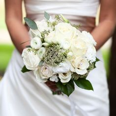 Bridal bouquet of white garden roses, ranunculus, and lisanthus