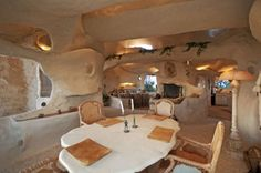 """Dining Room with view of Living Room in """"The Flintstone House"""" built for Dick Clark in Malibu, CA Unique Homes For Sale, Unusual Homes, Flintstone House, Fred Flintstone, Flintstone Cartoon, Caveman Style, Crazy Houses, Weird Houses, Malibu Homes"""