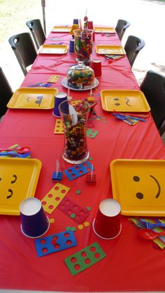 Lego Party Table set up -- yellow square plates, red and blue flatware and cups with Lego confetti