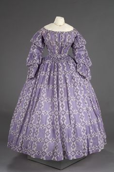 A: Bodice - Purple cotton with white and purple paisley print; roller print; off the shoulder neckline; long sleeves with three ruffled tiers; hook and eye closures on back; boning sewn into lining; fabric gathere vertically in front and back B: Skirt - long, full, plain skirt; gathered at waist; new waistband of white linen tape