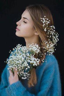 Девушка с закрытыми глазами, с волосами, заплетенными в косу, в голубой кофточке, прижимает к себе веточки с белыми цветами
