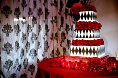 Three tiered black and white wedding cake with red rose accents, photo by Yvette Roman Photography