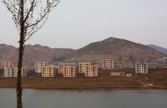 Buildings sit next to a small body of water in an unidentified North Korean town along the highway from Pyongyang to the southern city of Kaesong, photographed on April 17, 2011.