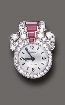 AN ART DECO RUBY AND DIAMOND LAPEL WATCH, BY JAEGER. With nickel-finished jewelled lever movement, the circular silvered dial, within a pavé-set diamond and calibré-cut ruby geometric surround, mounted in platinum, circa 1925. Dial signed Jaeger, P.L. Levy; movement signed Jaeger LeCoultre, numbered, case and caseback numbered.