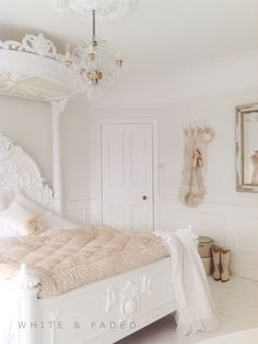 Gorgeous white bedroom with pale blush accent colors. French country bedroom. That bed crown is striking.