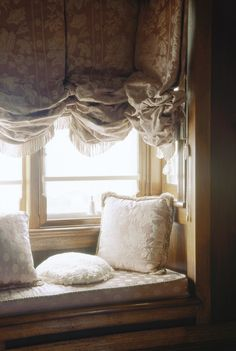 Traditional Austrian blind in a bay window with a matching upholstered box seat and scatter cushions