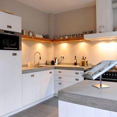 Mooie witte keuken gemaakt van sloophout met een keukenblad van beton.
