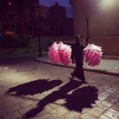 Walking back home with pink candies, the Egyptian vendor paints Cairo night with some vividness.  Photo by @peteraced  #Egypt #Cairo