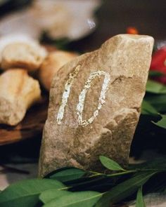 Locally foraged stones, gathered on the resort grounds the day before the celebration and painted with gold foil digits, served as table numbers at this winter wedding.
