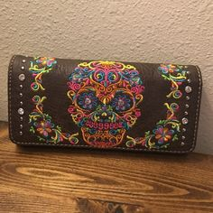 """NEW SUGAR SKULL WALLET! This adorable sugar skull wallet features a zipper inside and on the outside for coins. A place to hold your ID and multiple cards! It comes with a clip to be used as a wristlet! Leather! Sugar skull stitched in! Dark brown! 7.5"""" by 3.5"""" Bags Wallets"""