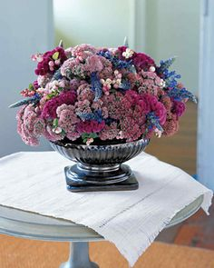 Jewel-Toned Flower Arrangement | Martha Stewart Living - Like a tapestry, this bouquet is a celebration of rich hues and textures. Round 'Autumn Joy' and fuzzy fuchsia Celosia provide fullness, while snowberries and blue 'Indigo Spires' function as accents.
