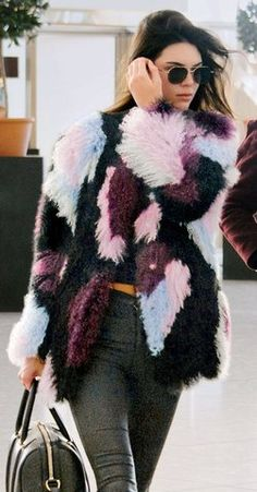 Kendall Jenner wears a colorful In an Elizabeth and James coat, high-waist pants, and black sunglasses