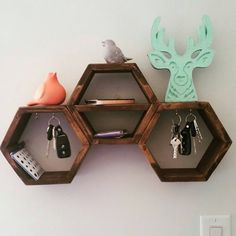 This is great for organization by the door. These mini hexagon shelves are all attached to each other. The middle hexagon has a shelf that is great for a cell phone or wallet. The outer hexagons have 2 hooks each for keys. The shelves are made from pine and stained a walnut colour. They are sealed with a wax. There are two hangers to ensure stability when hung. The shelf measures 11 1/2 inches tall and 21 1/2 inches wide.