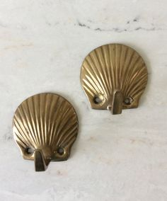 This is a pair of solid brass seashell wall hooks. Great for mounting on wood board or plaque for hanging keys, jewelry, towels, coat or just about anything! Great entry way decor item. Both in great vintage condition, all you need are screws ( not included). Measures each. 2 X 2 X 1.5 D  Thanks for shopping YellowHouseDecor!  Please visit my sisters shop for more vintage items ( ellansrelics02)