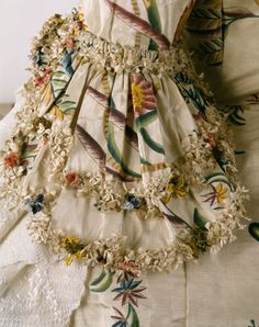The sleeves are finished with layers of engageants that are generally just basted in for easy detachment and washing and are thereby useful in keeping the valued dress clean. This painted silk gown is The Costume Institute's earliest example of the eighteenth- century fashion for exoticism and chinoiserie. It's is not, however, typical of the more commonly seen Chinese export silks, with their delicate and naturalistic designs. Robe à la Française