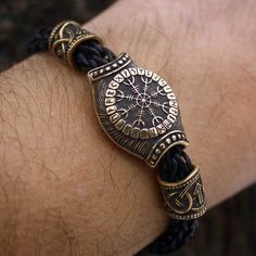 This is a genuine leather handmade braided bracelet with real solid bronze center piece, beads and wolf heads terminals.  The large center piece bead is double sided featuring a Vegvisir and Aegishjalmur runic staves. Two smaller beads feather Tiewaz and Algiz runes.  Vegvisir - a 'sign post