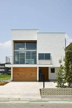 小野里信建築アトリエが手掛けたこちらの住まいはモダンな雰囲気のk木造住宅二階建て。緑広がる田園に真っ白で四角い建物がポン…