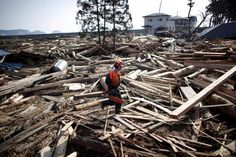 JAPAN-QUAKE/ An emergency worker walks amidst debris in an area hit by an earthquake and tsunami in Kuji, Iwate prefecture March 14, 2011. REUTERS/Aly Song (JAPAN - Tags: DISASTER ENVIRONMENT)