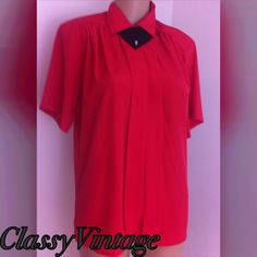 Silky red vintage blouse. Red silky fabric. Hidden button front with a cute black removable embellished tie. Short sleeves and pleated front. Straight hem. Bust 40. impressions of California Tops Blouses