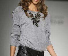 Leather shorts, gray sweatshirt top & statement necklace.