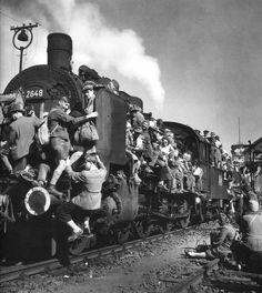 In a photograph by Margaret Bourke-White immediate postwar German refugees and displaced persons crowd a train leaving Berlin. (1945)