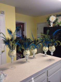 few blooms with large peacock feather make this small centerpiece