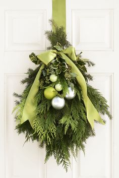 Bundled together with floral wire, fragrant greenery — yew, holly, spruce, and eucalyptus — makes a grand entrance. Use twine to knot ornaments onto a wooden floral pick; push pick tightly into the boughs. Finish with a bow-tied satin ribbon.