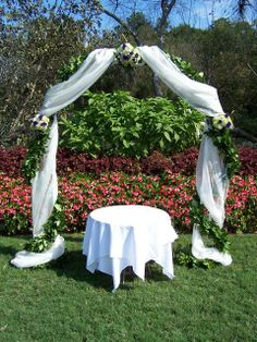 Arch covered in a garland of greenery, ivory organza and features 3 flower clusters