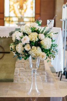 Lush white and green altar arrangement featuring greens, roses, peonies, and hydrangea by Plum Sage Flowers