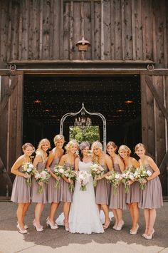 bridal party in front of a rustic barn. different color for the dresses and this would be perfect!