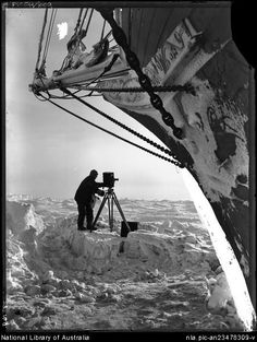 Hurley, Frank, 1885-1962. [Frank Hurley with camera on ice in front of the bow of the trapped Endurance in the Weddell Sea, Shackleton expedition, 1915] [picture] : [Antarctica]