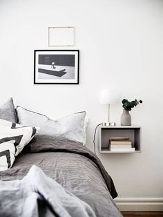 bedroom. floating box shelf as a bedside table. greys and white.